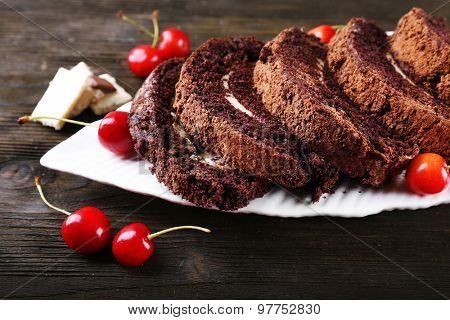 Delicious chocolate roll in white plate on wooden table, closeup