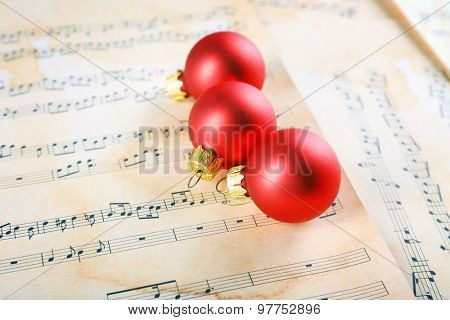 Christmas ball on music sheets background