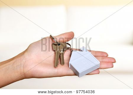 Female hand holding keys with house key chain on blurred sofa background