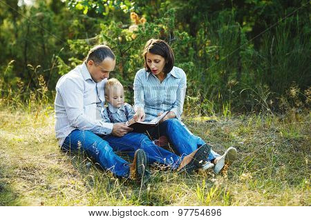 family reading book in park