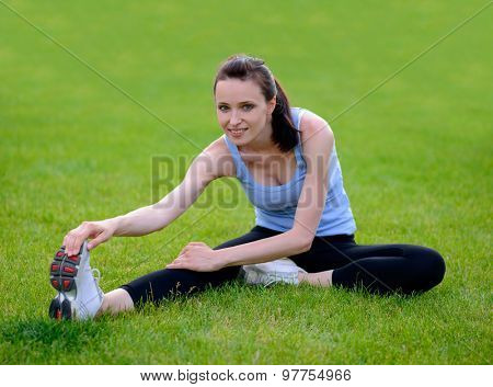 Beautiful Smiling Woman Doing Stretching Exercise on the Grass in the Park. Sport and Fitness Concept