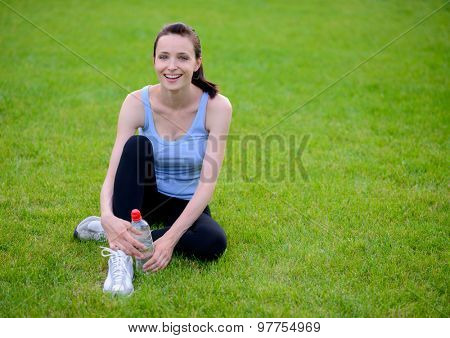 Beautiful Smiling Woman Relaxing on the Grass in the Park During Training. Sport and Fitness Concept