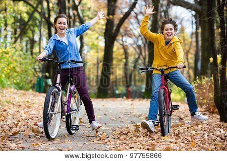 Urban biking - girl and boy riding bikes in city park