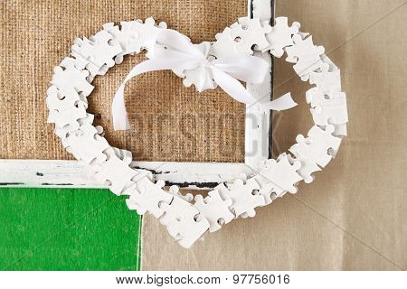 Puzzle made heart shape on color wooden background