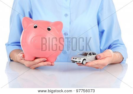 Female hands holding piggy bank and model of car, closeup