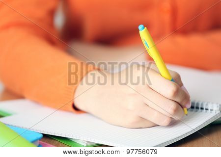 Female hand writing in notebook, close-up