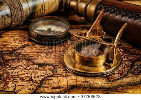Travel geography navigation concept background - old vintage retro compass with sundial and spyglass on ancient world map with copyspace