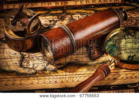 Travel geography navigation concept background - old vintage retro compass with sundial, spyglass and magnifying glass on ancient world map