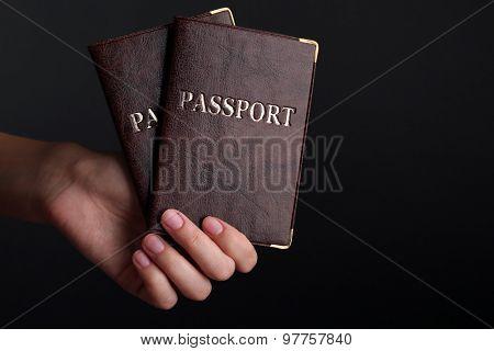 Female hand holding passports on dark background
