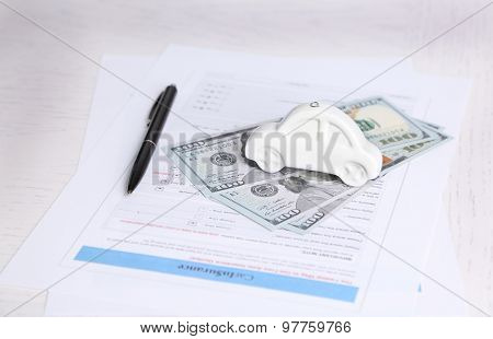 Toy car, money and documents on table. Car insurance concept