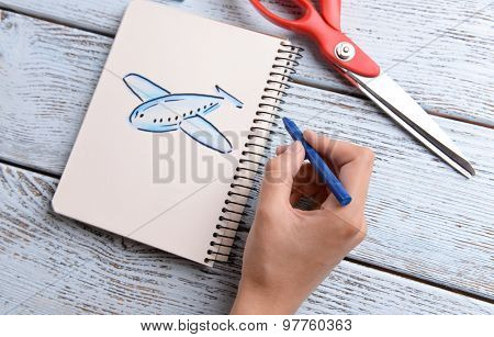 Female hand drawing plane in notebook on wooden table background