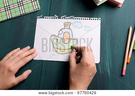 Female hands drawing picture on sheet of paper on wooden table background