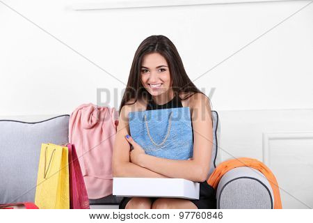 Beautiful young woman with shopping bags and boxes sitting on sofa in room