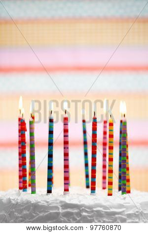 Birthday cake with candles on colorful striped background