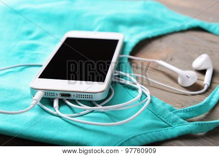 Mobile phone and earphones with t-shirt on wooden table, closeup