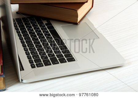 Laptop with book on table close up