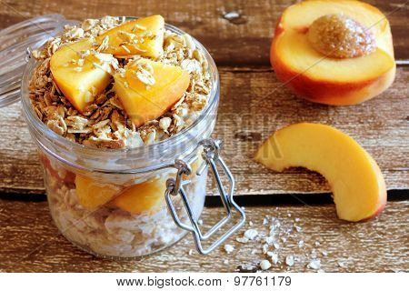 Overnight oats with peaches and granola on rustic wood