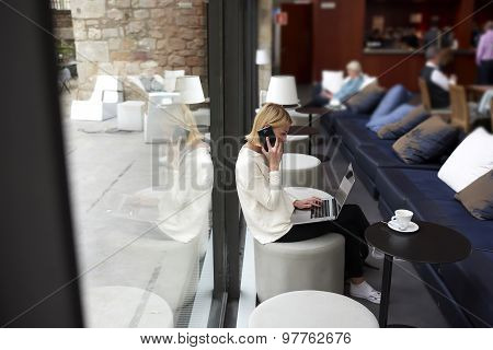 Female person using net-book and talk on smartphone during morning breakfast in modern coffee shop