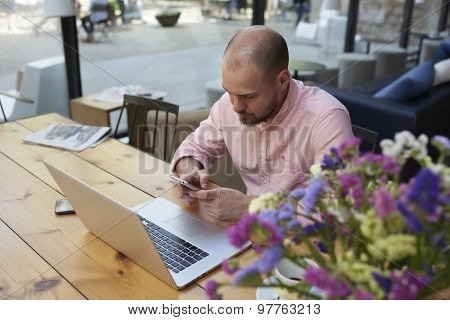 Businessman at coffee break text messaging while sitting at wooden table with open laptop computer