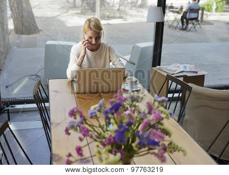 Businesswoman sitting front open laptop computer and talk on smartphone during morning breakfast
