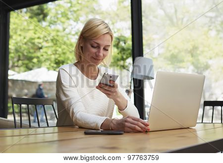 Female freelancer read text message on smartphone while sitting in coffee shop with beautiful garden