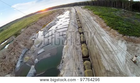 RUSSIA, VOSKRESENSK -?? JUL 1, 2014: Wagons with sand near the career during sunset. Aerial view. (Photo with noise from action camera)