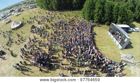 RUSSIA, NELIDOVO -?? JUL 12, 2014: Crowd of people listen concert during reconstruction Battlefield at Second World war. Aerial view. (Photo with noise from action camera)