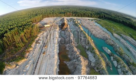 RUSSIA, VOSKRESENSK - JUL 1, 2014: Excavator is working near forest and old railway. Aerial view. (Photo with noise from action camera)