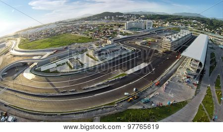 RUSSIA, SOCHI -?? JUL 28, 2014: Building site of stadium for racing near town and mountains at summer sunny day. Aerial view. (Photo with noise from action camera)