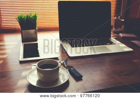 Home freelance desktop with open laptop computer and cup of coffee