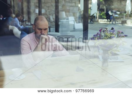 Puzzled and concerned male freelancer or student look to net-book in modern coffee shop interior