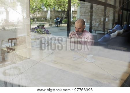 Worried businessman or entrepreneur sitting front open laptop computer in modern coffee shop