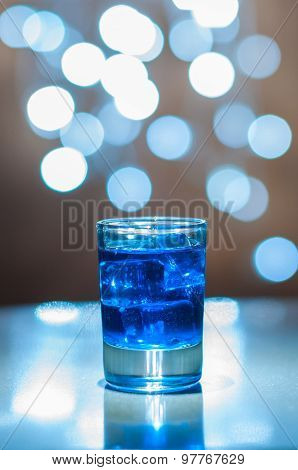 Alcoholic blue cocktail is in glass, on the bar wiyh magic bokeh light