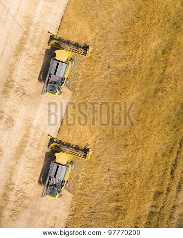 Aerial view of combine harvester on wheat field. Industrial background on agricultural theme.