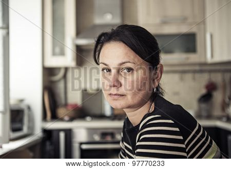 Thoughtful woman in her apartment interior.