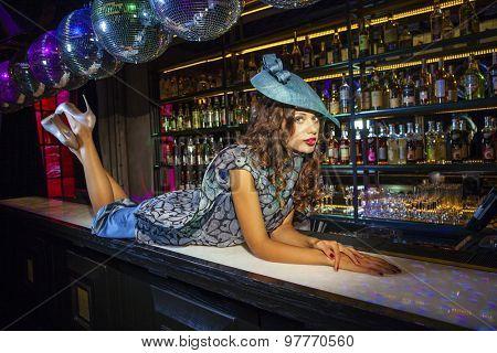 Fashionable beautiful girl in a stylish hat in night club