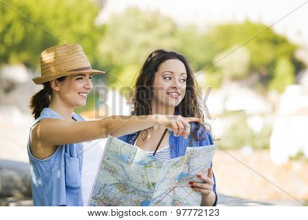 Two beautiful female friends searching a place on the map