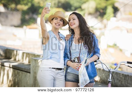 Two beautiful female friends making a selfie with cellphone