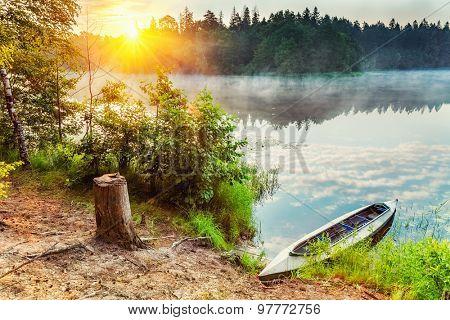 Canoe on a lake at foggy morning
