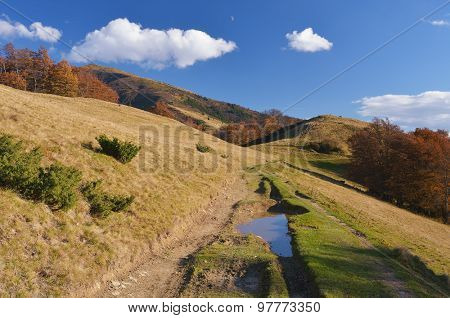 Autumn in the mountains. Sunny day with cumulus clouds. Road with puddles and pools of water. Carpathians, Ukraine, Europe