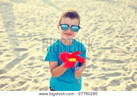 Little Boy With Pinwheel In Vintage Style On Beach
