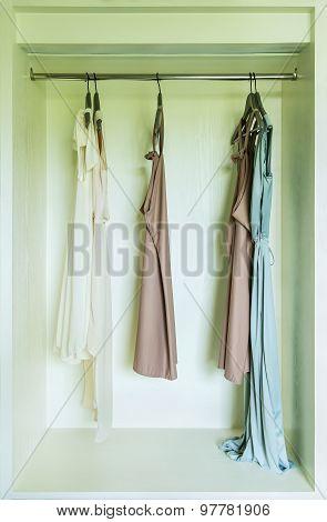 Row Of Dress Hanging On Coat Hanger In Wardrobe
