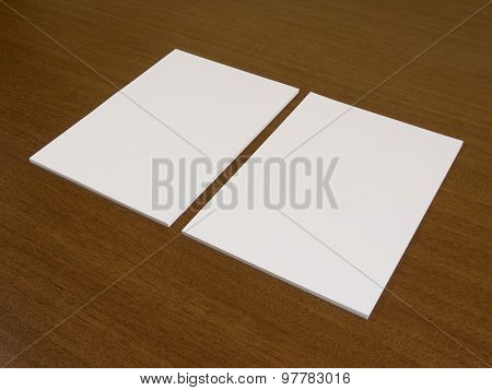 Two blank white papers on a wooden background.