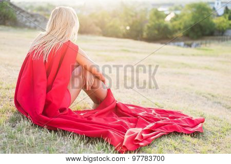 Resting superhero, blonde wonderwoman posing outdoor