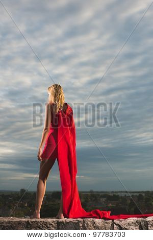 Young woman posing as superhero over the city