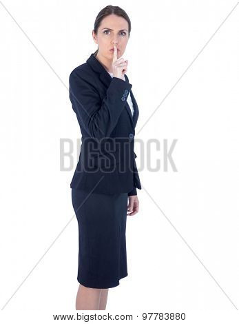 Pretty businesswoman asking for silence against a white wall