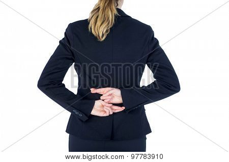 Close up pretty businesswoman with fingers crossed against a white wall