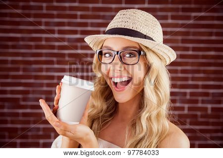 Portrait of gorgeous smiling blonde hipster presenting take-away cup against red brick background