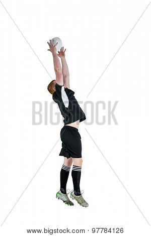 Profile view of a rugby player catching a rugby ball