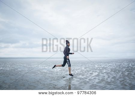 Fit girl jogging on cold day at the beach